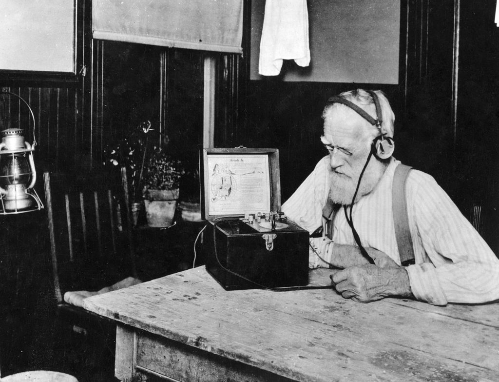 "Farmers poked the ""cat's whisker"" of their crystal sets around on a piece of quartz until they picked up the crop reports and then listened intently. The information they heard through their earphones helped them decide what to raise and when to sell. This farmer is listening to a 1923 broadcast from Washington, D. C."